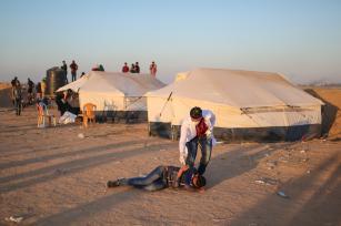 """Un médico ayuda a un palestino herido durante el """"Día de la Tierra"""", que conmemora el asesinato de seis palestinos por las fuerzas israelíes en 1976, en Khan Yunis, Gaza, 1 de abril de 2018 (Ashraf Amra- Anadolu Agency)"""