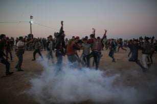 """Las fuerzas de ocupación israelíes usan gas lacrimógeno contra los palestinos durante el """"Día de la Tierra"""", que conmemora el asesinato de seis palestinos por las fuerzas israelíes en 1976, en Khan Yunis, Gaza, 1 de abril de 2018 (Ashraf Amra- Anadolu Agency)"""