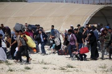 Refugiados sirios con sus pertenencias pasan por la puerta fronteriza de Oncupinar para llegar a sus lugares de origen antes de Eid al-Adha en Kilis, Turquía, el 29 de agosto de 2017 [Ensar Özdemir / Agencia Anadolu]
