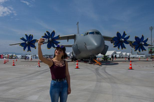 Una mujer se hace un selfie con un avión mientras se exhiben aviones y equipos aeronáuticos durante el 'Eurasia Airshow' en la Terminal Internacional del Aeropuerto de Antalya en Antalya, Turquía, 26 de abril de 2018 [Orhan Çiçek / Agencia Anadolu]