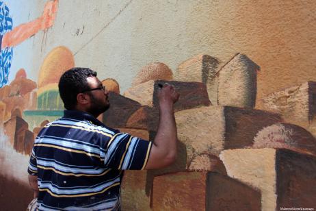 Artistas palestinos pintan un mural en Gaza después de la apertura de la embajada de Estados Unidos en Jerusalén, 16 de mayo de 2018 [Mahmoud Ajour / Apaimages]