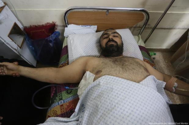 El periodista palestino y corresponsal de MEMO en Gaza, Motasem Dalloul, fue hospitalizado después de ser herido por un francotirador israelí mientras cubría la Gran Marcha del Retorno cerca de la frontera oriental de Gaza el 11 de mayo de 2018 [Mohammad Asad / Middle East Monitor]