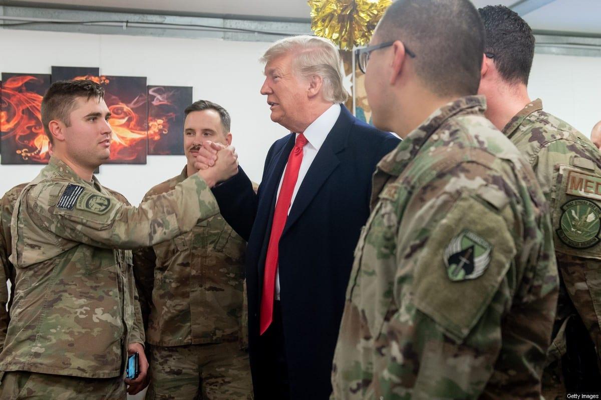 El presidente de los Estados Unidos, Donald Trump, saluda a los miembros del ejército de los Estados Unidos durante un viaje no anunciado a la base aérea de Al Asad en Irak el 26 de diciembre de 2018. (Foto de SAUL LOEB / AFP) (El crédito de la foto debe leer SAUL LOEB / AFP a través de Getty Images)