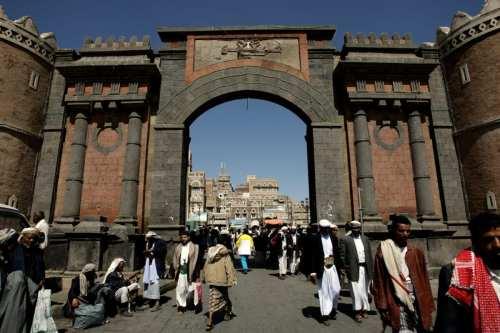 Los yemeníes caminan bajo la emblemática Puerta de Yemen que conduce a la antigua ciudad de Sanaa el 8 de noviembre de 2009 [MARWAN NAAMANI/AFP vía Getty Images]