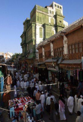 """La gente pasa por delante de la histórica casa de """"Nur Wali"""" en el antiguo mercado de Souq al-Alawi en la ciudad portuaria saudí de Jeddah el 28 de noviembre de 2008 [KHALED DESOUKI/AFP via Getty Images]."""