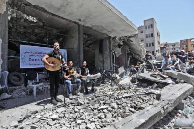 Palestinos se apresentam sobre as ruínas de uma casa destruída por bombas de aviões israelenses, em Gaza,14 de maio de 2019 [Mohammed Asad/Middle East Monitor]