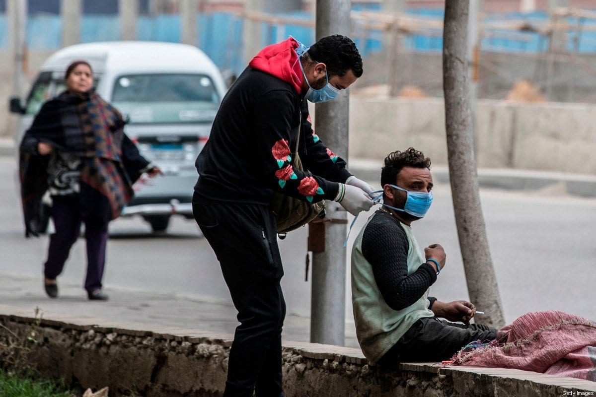 Um voluntário (esq) prende máscara de um homem em rua da capital egípcia, Cairo, em 20 de março de 2020 [Khaled Desouki/ AFP/ Getty Images]