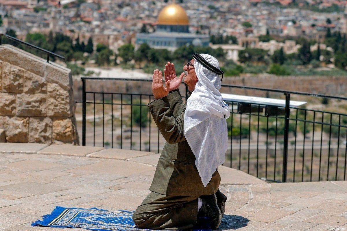 Idoso palestinos realiza oração de sexta-feira durante o mês sagrado do Ramadã, com a Cidade Velha de Jerusalém ao fundo, diante da crise do coronavírus, conforme fechamento do complexo de Al-Aqsa, em 8 de maio de 2020 [Ahmad Gharabli/AFP/Getty Image]