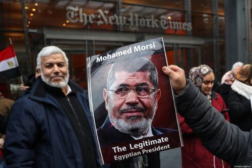 Homem segura um pôster do falecido ex-presidente egípcio Mohammed Morsi durante um protesto em Nova York, EUA em 2 de março de 2019 [Atılgan Özdil/ Agência Anadolu]