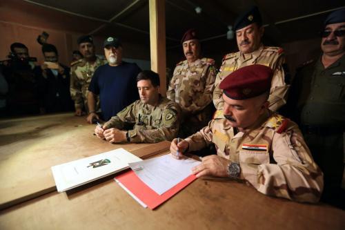 Comandante da 32ª Brigada Ahmed Qasim (R) participa da cerimônia de entrega dos EUA da base militar de al-Qaim, onde foi usada por tropas da coalizão liderada pelos EUA, na fronteira Iraque-Síria em Província de Anbar, no Iraque, a oeste de Bagdá, em 19 de março de 2020. [Murtadha Al-Sudani - Agência Anadolu]