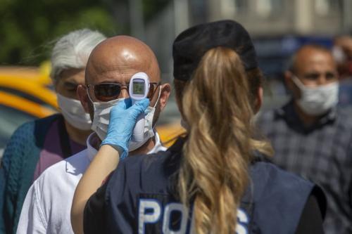 Oficial de polícia mede temperatura de um homem à medida que restrições nacionais diante do coronavírus são atenuadas em Ancara, Turquia, 28 de maio de 2020 [Aytaç Ünal/Agência Anadolu]