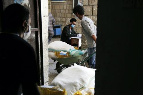 Assistência alimentar enviada pelo Programa Alimentar Mundial (PAM) das Nações Unidas é distribuída a pessoas carentes diante da pandemia de coronavírus, em Sanaa, capital do Iêmen, 3 de junho de 2020 [Mohammed Hamoud/Agência Anadolu]