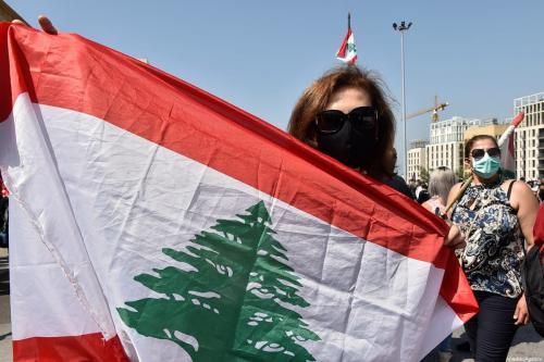 Mulher segura bandeira libanesa em Beirute, Líbano, 6 de junho de 2020 [Hussan Chbaro/Agência Anadolu]