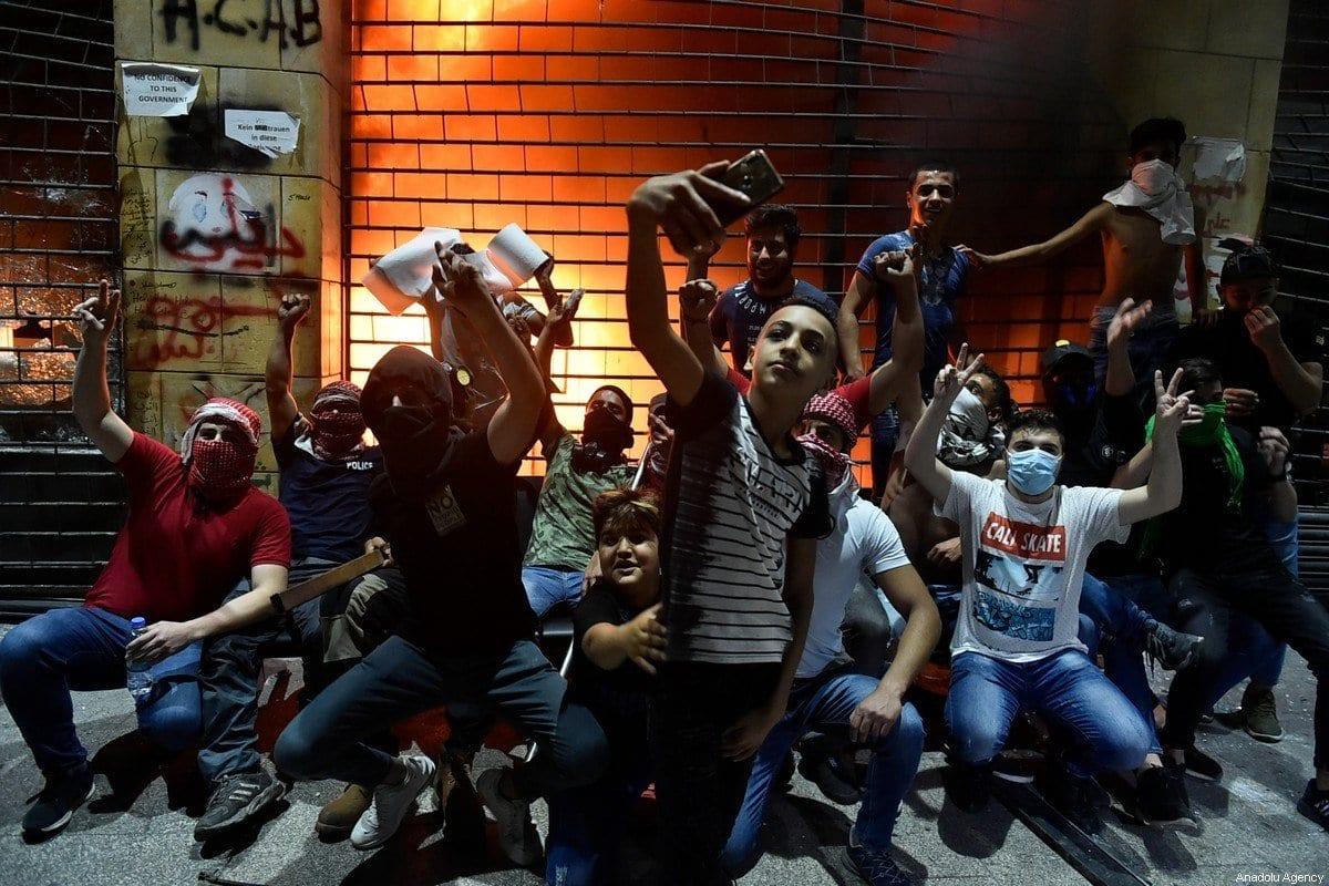 Manifestantes tiram selfies em frente a uma loja atacada durante manifestação contra as duras condições econômicas e colapso da moeda libanesa, agravados pela pandemia de coronavírus, na Praça Riad al Sohl, em Beirute, Líbano, 12 de junho de 2020 [Hussam Shbaro/Agência Anadolu]