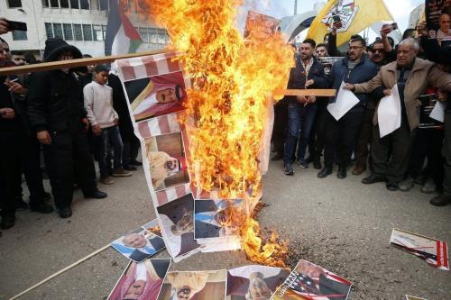"""Manifestantes palestinos queimam retratos de líderes regionais – o Rei do Bahrein Hamad al-Khalifa, o Primeiro-Ministro dos Emirados Árabes Unidos Mohammed bin Rashid al-Maktoum, e novo governante real de Omã Haitham bin Tariq –, durante protesto contra o """"plano de paz"""" dos Estados Unidos, em Hebron (Al-Khalil), Cisjordânia ocupada, 30 de janeiro de 2020 [Hazem Bader/AFP/Getty Images]"""