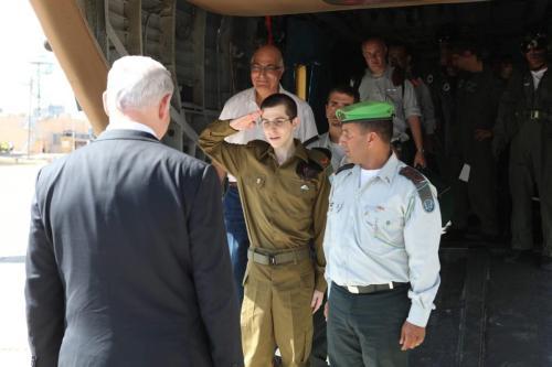 O soldado israelense libertado, Gilad Shalit, cumprimenta o primeiro-ministro de Israel Benjamin Netanyahu depois de desembarcar em uma base aérea do exército israelense. Shalit foi libertado em 18 de outubro de 2011 após ser mantido como prisioneiro de guerra por cinco anos e meio na Faixa de Gaza ocupada [IDF Online]