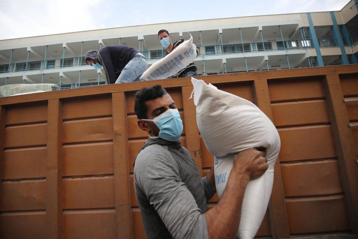 Agência das Nações Unidas para Refugiados da Palestina (UNRWA) distribui assistência alimentar em Gaza, 2 de abril de 2020 [Mohammed Asad/Monitor do Oriente Médio]
