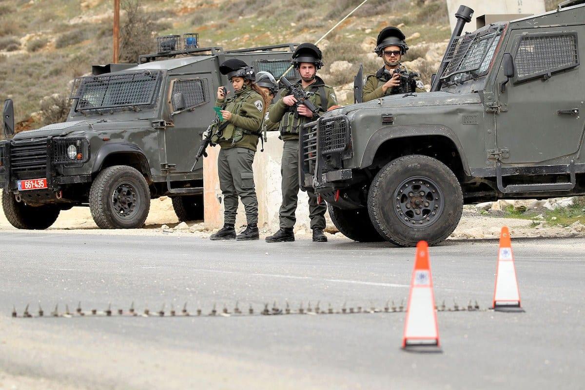 Soldados israelenses revistam carro em um posto de controle em Hebron, Cisjordânia, em 26 de janeiro de 2017 [Wisam Hashlamoun / Anadolu Agência]