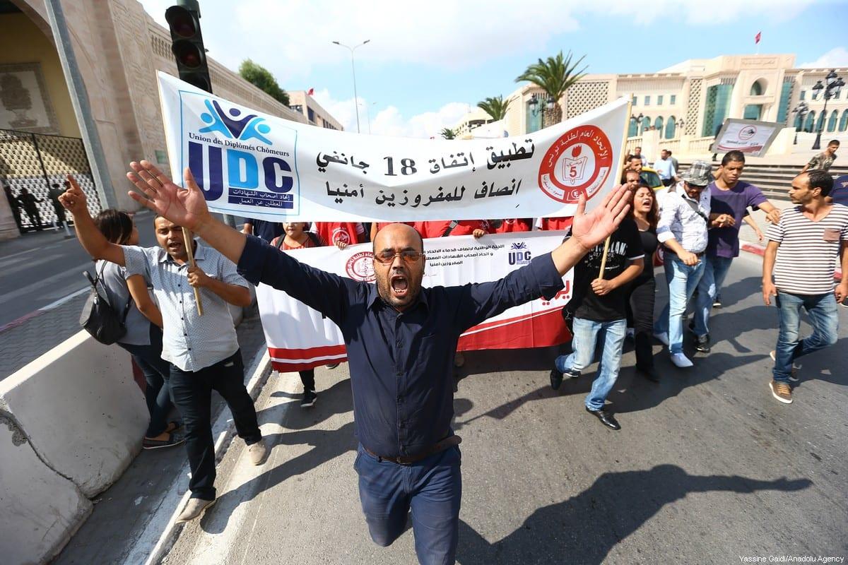 Manifestantes, cujo trabalho fora restrito a gabinetes públicos, realizam um protesto por emprego, em frente à sede de governo, em Túnis, Tunísia, 25 de setembro de 2017 [Yassine Gaidi/Agência Anadolu]