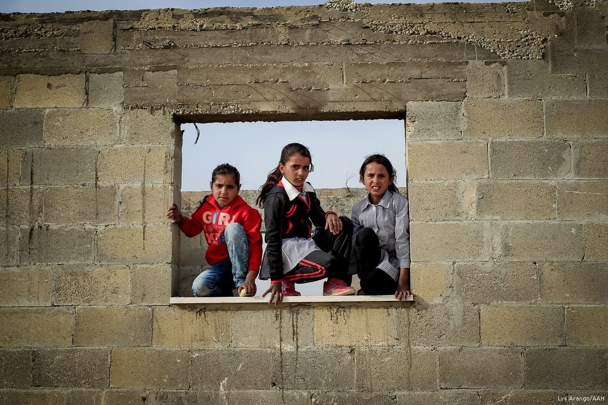 Crianças palestinas posam na frente de uma escola. Crianças da comunidade beduína correm o risco de perder a escola se os tribunais israelenses decidirem por sua demolição. [Lys Arango / AAH]