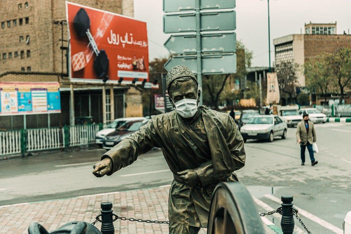 Uma estátua ganha máscara facial enquanto o governo iraniano remove gradualmente as precauções contra a nova pandemia de coronavírus, permitindo a reabertura de lojas. Em Tabriz, Irã, em 12 de abril de 2020. [Stringer/Anadolu Agency]