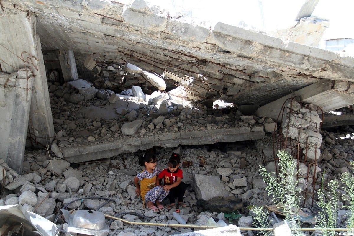 Meninas palestinas brincam nos escombros de uma casa, que foi destruída durante a guerra de 50 dias entre militantes de Israel e do Hamas no verão de 2014, em Rafah, no sul da Faixa de Gaza, em 29 de julho de 2015 [Abed Rahim Khatib/ ApaImages]