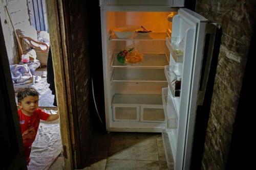 Criança libanesa ao lado de uma geladeira vazia em Beirute, capital do Líbano, diante da severa crise econômica do país e os altos índices de pobreza e miséria, em 17 de junho de 2020 [Ibrahim Chalhoub/AFP/Getty Images]