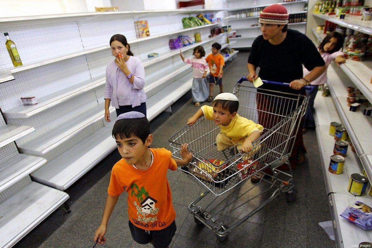 Colonos realizam compras em um supermercado no assentamento ilegal de Neve Dekalim, na Faixa de Gaza, em 10 de agosto de 2005 [Nicolas Asfouri/AFP/Getty Images]