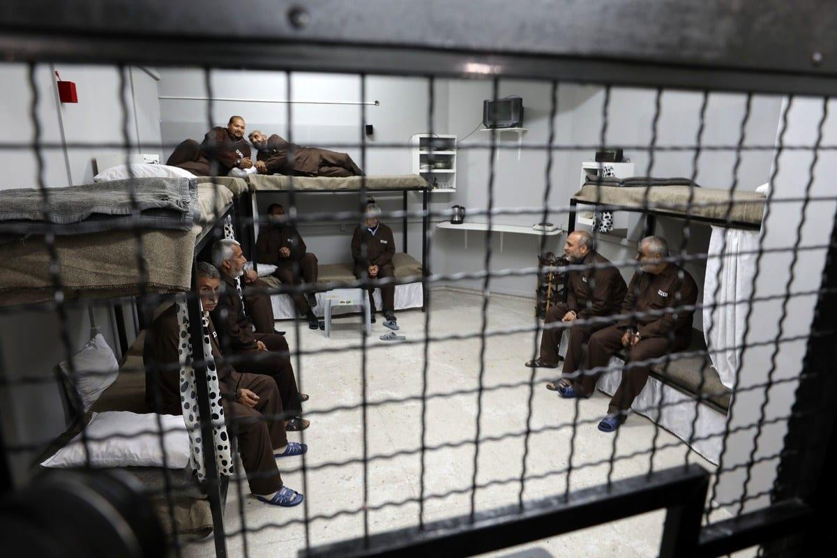 Ativistas palestinos sentam-se em uma prisão simulada durante protesto em solidariedade aos prisioneiros palestinos nas cadeias de Israel, em 9 de abril de 2019 [Mahmoud Nasser/Apaimages]
