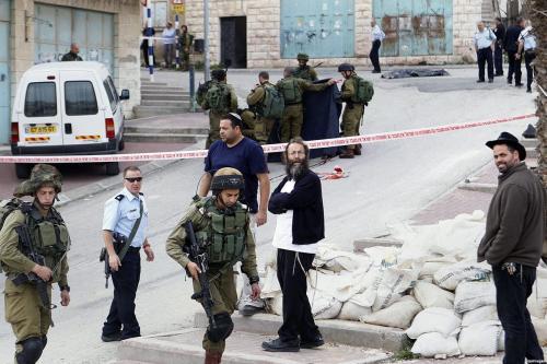 Colonos observam enquanto forças israelenses evacuam o corpo de Abdel Fattah al-Sharif, morto por Elor Azaria, médico do exército israelense, Hebron (Al-Khalil), Cisjordânia ocupada, 24 de março de 2016 [foto de arquivo]