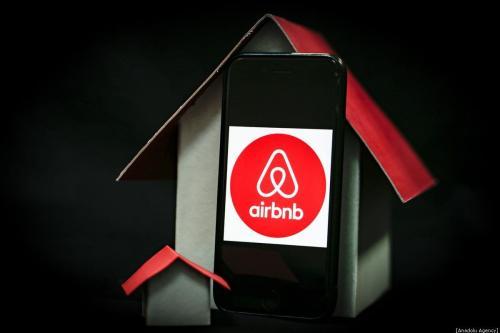 Uma tela de telefone exibe o logotipo do Airbnb com uma maquete de casa ao lado, em 30 de dezembro de 2019 [Metin Aktaş/Agência Anadolu]