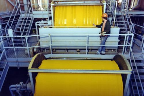 """Trabalhadores com capacete monitoram a produção de """"yellowcake"""", um concentrado de urânio em pó, durante um processo de filtragem de três tambores, 1975. [Departamento de Energia dos EUA/ Smith Collection/ Getty Images]"""