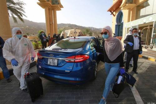 Mulher usando máscara deixa um estância marítima onde ficou em quarentena por 14 dias, a aproximadamente 60 quilômetros ao sul da capital jordaniana, Amã, em 30 de março de 2020 [Khalil Mazraawi/ AFP via Getty Images]