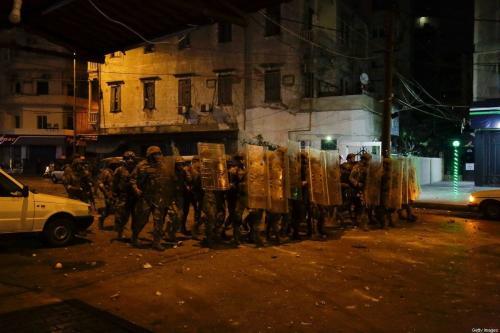Soldados do exército libanês avançam e manifestantes jogam pedras em confrontos durante a noite na cidade norte do Líbano em Trípoli em abril 28, 2020 [Ibrahim Chalhoub/ AFP via Getty Images]
