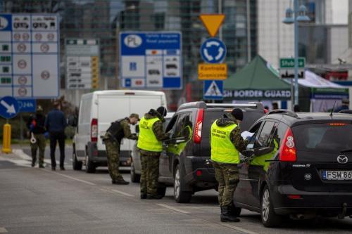 Guardas de fronteira inspecionam carros antes de atravessarem da Alemanha à Polônia, na divisa entre Slubice e Frankfurt (Oder), em 20 de março de 2020 [Maja Hitij/Getty Images]