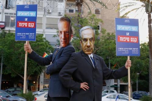Manifestantes vestem máscaras do Primeiro-Ministro de Israel Benjamin Netanyahu e seu parceiro de coalizão e Ministro da Defesa Benny Gantz, durante protesto contra o plano israelense de anexar grandes partes da Cisjordânia ocupada, na Praça Rabin, Tel Aviv, 23 de junho de 2020 [Jack Guez/AFP/Getty Images]