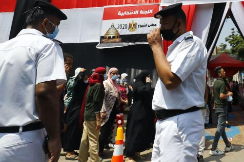 Cidadãos egípcios, com máscara devido à pandemia de covid-19, aguardam em fila em uma estação eleitoral, para votar no novo Senado, em 11 de agosto de 2020 [Khaled Desouki/AFP/Getty Images]
