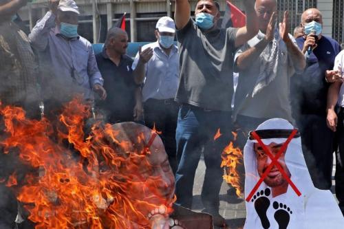 """Manifestantes palestinos incendiaram cartazes com os rostos do primeiro-ministro israelense Benjamin Netanyahu e do príncipe herdeiro de Abu Dhabi Sheikh Mohammed bin Zayed al-Nahyan durante uma manifestação em Nablus, na Cisjordânia, ocupada em 14 de agosto de 2020 contra um Acordo mediado pelos EUA entre Israel e os Emirados Árabes Unidos para normalizar as relações. É o terceiro acordo que o estado judeu faz com uma nação árabe, uma mudança histórica que torna o estado do Golfo apenas o terceiro país árabe a estabelecer laços diplomáticos plenos com o estado judeu. A liderança palestina expressou sua """"forte rejeição e condenação"""" do acordo e anunciou que retiraria seu enviado dos Emirados Árabes Unidos.. (Jaafar Ashtiyeh/ AFP)"""