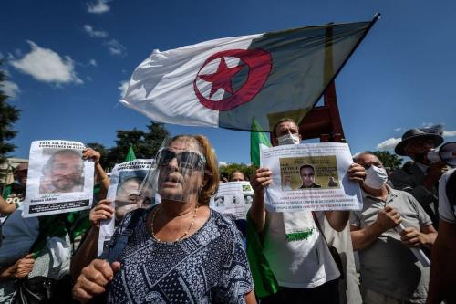 """Mulher com máscara protetora participa de uma manifestação em frente ao Escritório das Nações Unidas em Genebra contra as """"prisões arbitrárias"""" na Argélia, em 23 de agosto de 2020. [Fabrice Coffrini/ AFP via Getty Images]"""