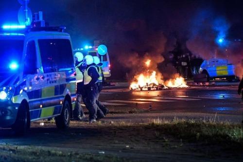 Policiais isolam a área onde pneus foram queimados e fogos de artifício foram disparados durante protestos da extrema-direita no bairro de Rosengard, na cidade de Malmo, Suécia, 28 de agosto de 2020 [TT News Agency/AFP/Getty Images]