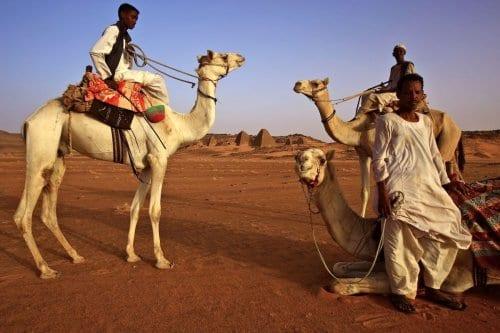 Homens sudaneses montam camelos em torno das pirâmides meroíticas de Bajarawiya, perto de Hillat ed Darqab [Ashraf Shazly/AFP/Getty Images]
