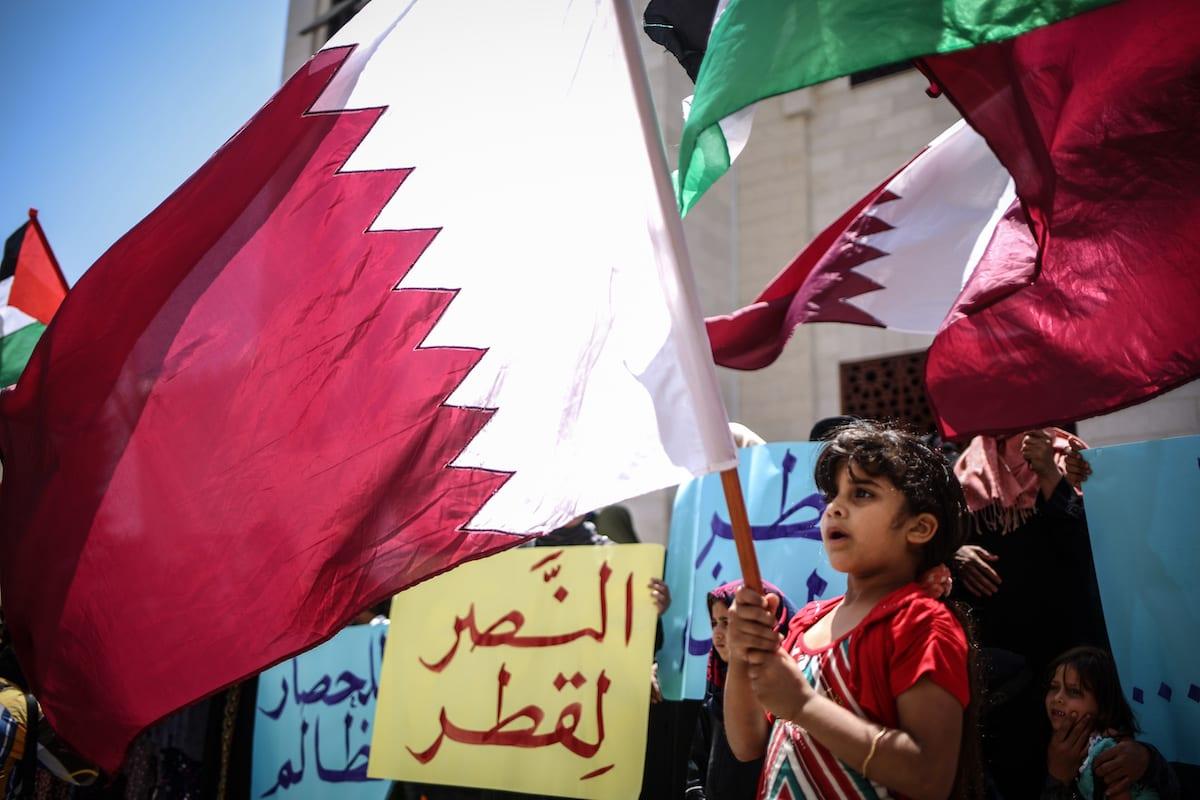 Palestinos exibem bandeiras catarianas durante protestos em apoio ao Catar, em Khan Younis, Gaza, 14 de junho de 2017 [Ali Jadallah/Agência Anadolu]
