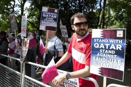 Manifestantes seguram cartazes durante um protesto contra a agressão liderada pela Saudita-Emirados Árabes Unidos no Catar em 17 de junho de 2017 [Isabel Infantes / Anadolu Agência]