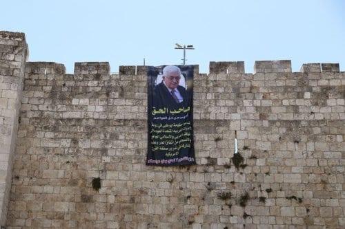 Presidente da Autoridade Palestina Mahmoud Abbas é retratado em um cartaz pendurado nos muros da Cidade Velha de Jerusalém, em 20 de agosto de 2020. Em árabe: 'O verdadeiro dono é mais forte do que todo o dinheiro. Exortamos o governo de Abu Dhabi nos Emirados Árabes Unidos a retomar a posição árabe e islâmica, revogar este pacto vergonhoso e não tomar parte no chamado acordo do século dos Estados Unidos. As feridas de Jerusalém não serão tratadas com o sal de seu dinheiro' [Ammar Awad/Twitter]