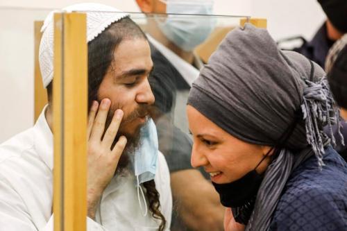 Amiram Ben-Uliel, extremista judeu condenado pelo incêndio criminoso de Duma, fala com sua esposa por trás de uma vidraça durante audiência de sentença, no tribunal distrital da cidade de Lod, no centro de Israel, 9 de junho de 2020 [Menahem Kahana/AFP/Getty Images]