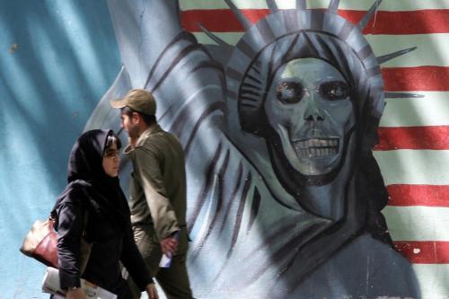 Iranianos caminham em frente a um mural crítico aos Estados Unidos, na antiga embaixada americana em Teerã, 8 de maio de 2006 [Atta Kenare/AFP/Getty Images]