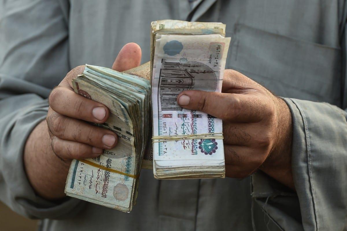 Comerciante egípcio conta dinheiro no mercado de Ashmun, Egito, 15 de agosto de 2018 [Mohamed el-Shahed/AFP/Getty Images]