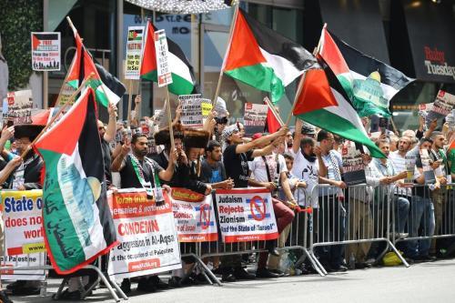 Manifestantes exibem cartazes e bandeiras palestinas em protesto contra Israel nos Estados Unidos, em 22 de julho de 2017 [Volkan Furuncu/Agência Anadolu]