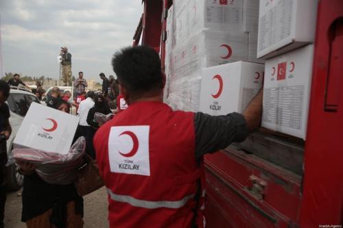 Membros do Crescente Vermelho Turco distribuem ajuda humanitária aos civis em Tal Abyad, Síria em 19 de outubro de 2019 [ Ömer Alven / Agência Anadolu]
