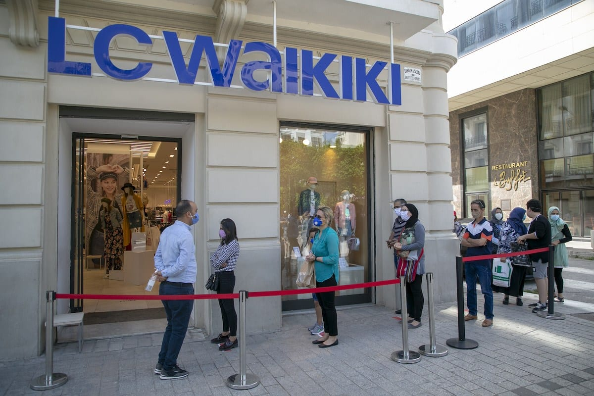 Pessoas de máscara fazem fila em frente a lojas, devido a restrições de acesso decorrentes do novo coronavírus, em Túnis, capital da Tunísia, 11 de maio de 2020 [Yassine Gaidi/Agência Anadolu]